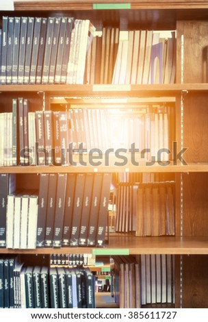 Many book sort stacked on wooden shelf in library