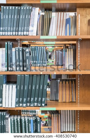 Many book sort stacked on wooden shelf in library - stock photo