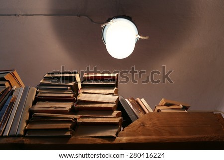 Many books on bookshelf with light bulb in library - stock photo