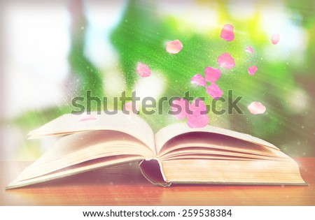 Many books with flying petals on table on bright background