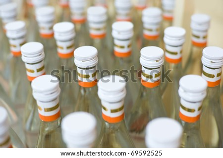 many bottles of vodka at production line of distillery - stock photo