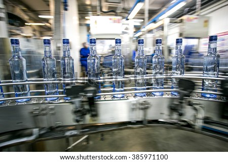 Many bottles on conveyor belt in factory, production of russian traditional alcohol drink vodka - stock photo