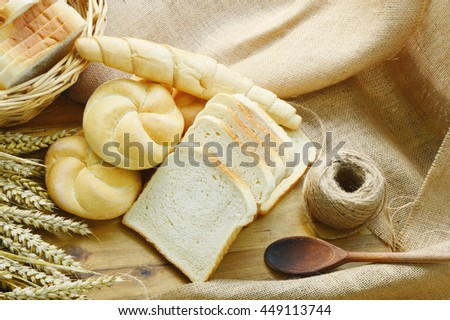 Many bread  in the basket on wooden floor with sack cloths.  Kaiser roll and sliced white bread .