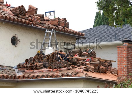 Many bricks piled on the roof of a house, process of removing multiple layers of a tile roof. Clay tile generally weighs more than concrete, anywhere from 1,000 to 1,500 pounds per 10' by 10' square.