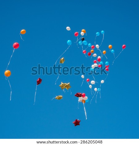 many bright baloons in the blue  sky - stock photo