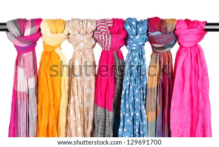 Many bright female scarfs isolated on white