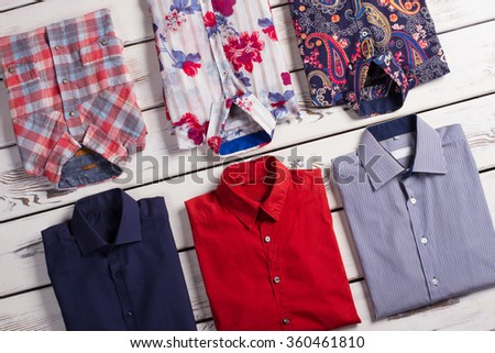 Many bright modern men's shirts with different colors and prints on wooden store shelf. - stock photo