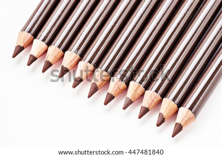 Many brown eyebrow pencils on white background. - stock photo