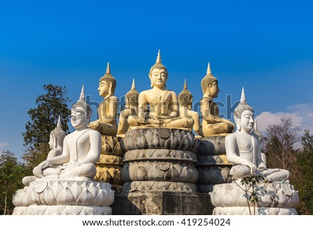 many buddha statue sitting on blue sky background in Thai temple.  - stock photo