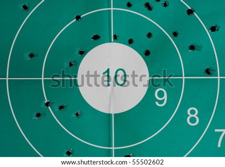 Many bullet holes in the target and intact bulls-eye - inaccuracy concept - stock photo