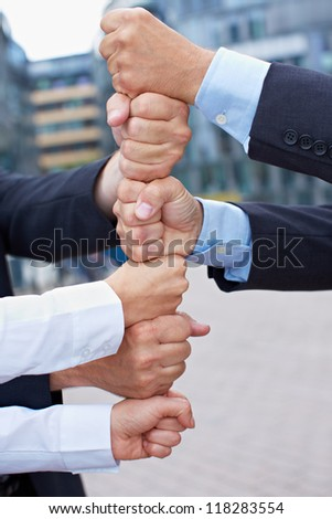 Many business people building a tower of their clenched fists - stock photo