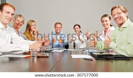 Many business people holding thumbs up together in a meeting - stock photo