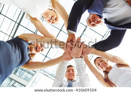 Many business people stacking their hands as concept for teamwork - stock photo