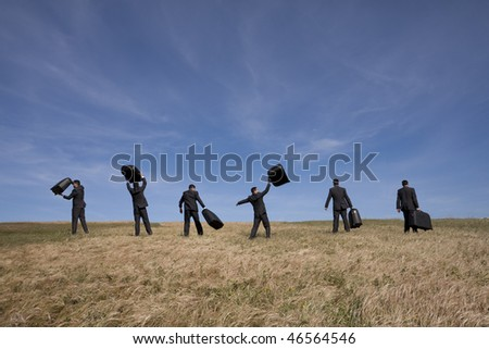 many businessman in the field walking with their luggage