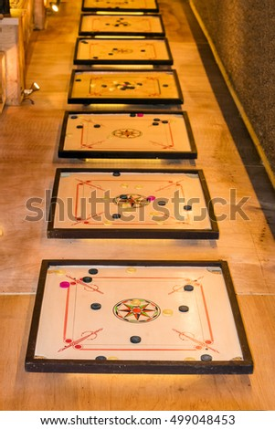 Many carrom boards and coins arranged in a row.