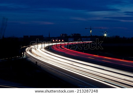 many cars are driving at night on a highway and create light trails. - stock photo