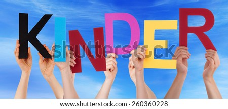 Many Caucasian People And Hands Holding Colorful Letters Or Characters Building The German Word Kinder Which Means Kids On Blue Sky - stock photo