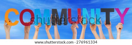 Many Caucasian People And Hands Holding Colorful Straight Letters Or Characters Building The English Word Community On Blue Sky - stock photo