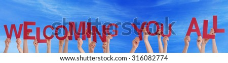 Many Caucasian People And Hands Holding Red Letters Or Characters Building The English Text Welcoming You All. Blue Sky