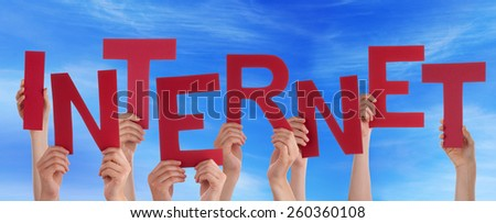 Many Caucasian People And Hands Holding Red Letters Or Characters Building The English Word Internet On Blue Sky - stock photo