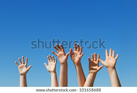 Many children hands raised up against the blue sky with copy space - stock photo