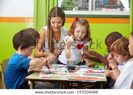 Many children painting together with nursery teacher in a kindergarten - stock photo