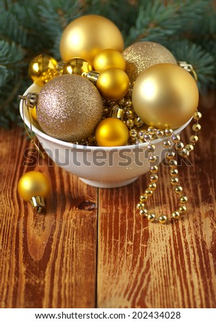 Many Christmas balls on a plate. Background of an old wooden table. Christmas background. Christmas card. - stock photo