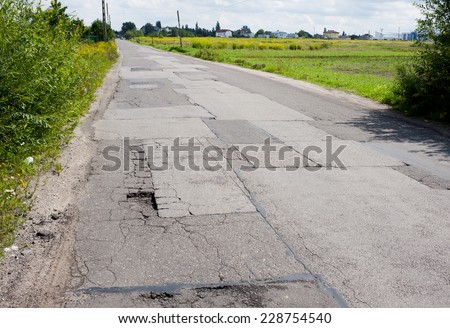Many chuckholes in asphalt damaged road and green bush around in Warsaw, Poland, horizontal orientation, nobody.