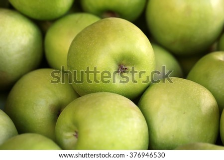 Many clean organic fresh tasty ripe green apples crop fruit full of vitamin for healthy eating diet ball form for sale on natural background, horizontal picture - stock photo