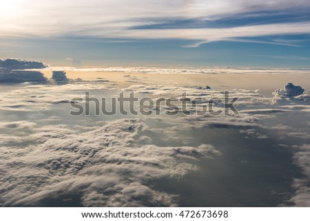 Many cloud in Flying above sunrise, view from outside airplane
