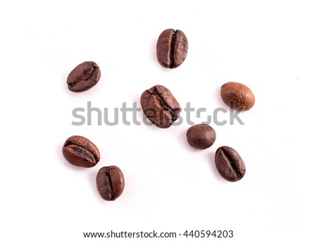 Many coffee beans in the background. Texture of the coffee beans on a white background. Smelly, saturated brown arabic coffee beans