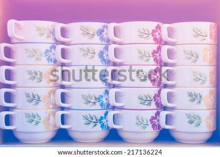 Many coffee cups lined with pastel tones. - stock photo