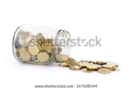 many coins spilling out of a glass jar and isolated on a white background  - stock photo