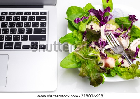 Many color salad with business laptop isolated on white serve on office table - stock photo