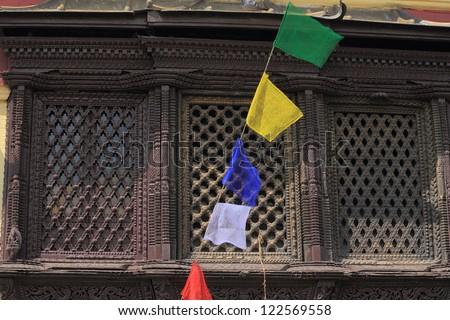 Many colored buddhist prayer flags before richly carved wooden nepali window, in the area surrounding the Swayambhunath Stupa,Kathmandu, Nepal. - stock photo