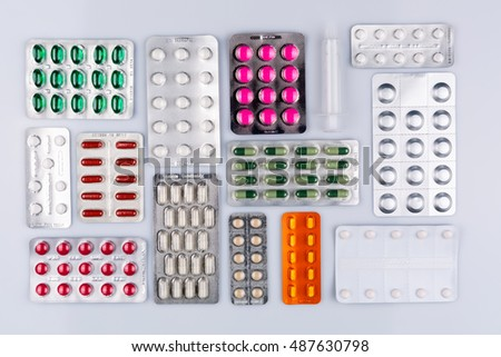 many colorful blisters with pills inside arranged on white