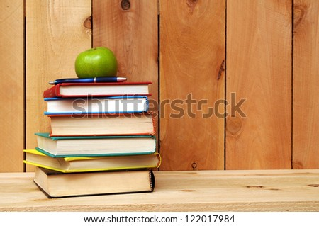 many colorful books and apple on shelf - stock photo
