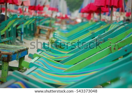Many colorful chair and red umbrella on the beach for relaxation activity for traveler in holiday
