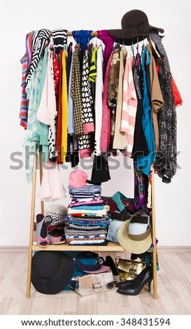 Many colorful clothes on hangers in a store. A lot of clothes and accessories hanging on a rack nicely arranged on hangers and in piles. - stock photo