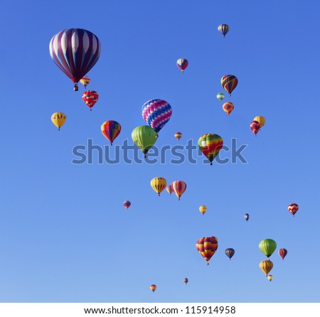 Many colorful hot air balloons in blue sky at balloon fiesta - stock photo