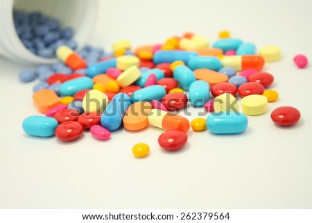 many colorful medicine pills pouring out of the white bottle on a white background