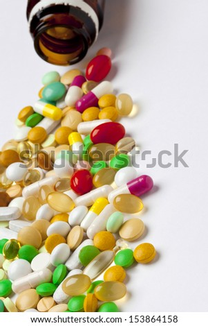 Many colorful medicines spilling out of a bottle - stock photo