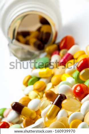Many colorful medicines spilling out of a bottle