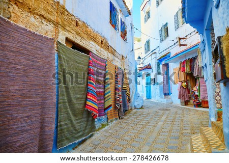 Many colorful Moroccan carpets for sale on a street in Medina of Chefchaouen, Morocco, small town in northwest Morocco known for its blue buildings - stock photo
