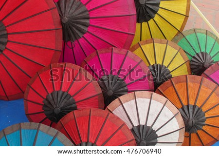 Many colorful opened umbrellas made of paper and wood