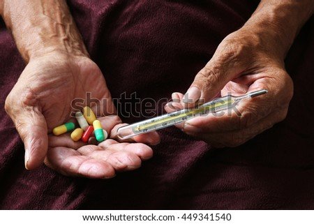 Many colorful pills and thermometer in the old hands. Painful old age. Health care of older people - stock photo