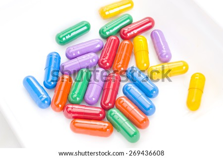 many colorful pills on a white background