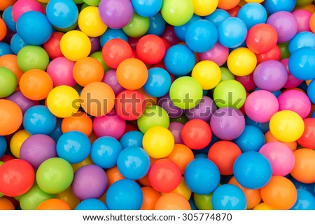 Many colorful plastic balls in a kids' ballpit at a playground. - stock photo