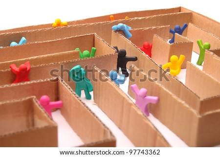 many colorful plasticine people running through paper maze - stock photo
