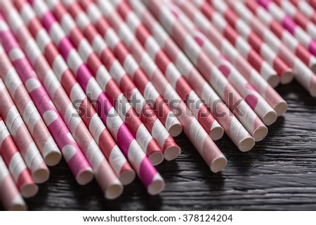 Many colorful straws lying on a dark textured surface. Straws are red and white, pink and white, purple and white. There is free space below the straws. Close-up photo. Horizontal. - stock photo